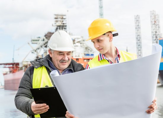 Shipbuilding engineer discusses documents with a student. Experienced worker wearing white safety helmet explains technical issues to a manual labourer.
